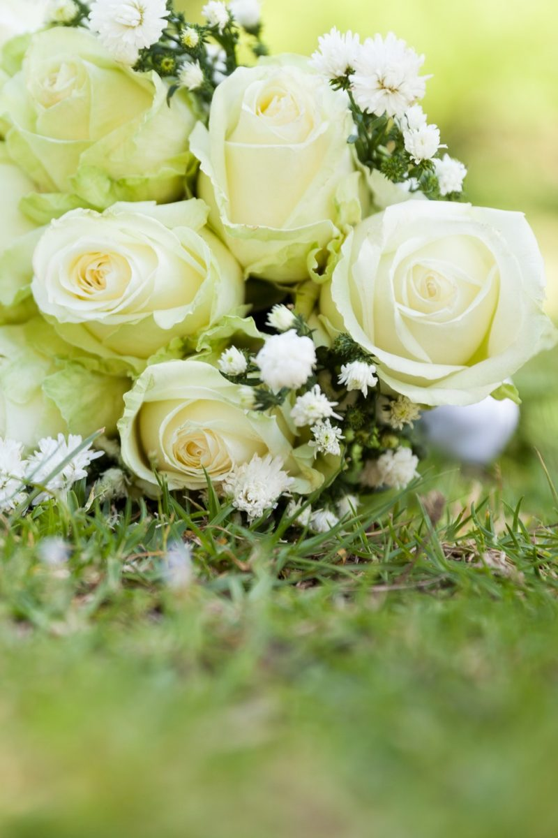 Close-up of bridal bouquet on grass at the park